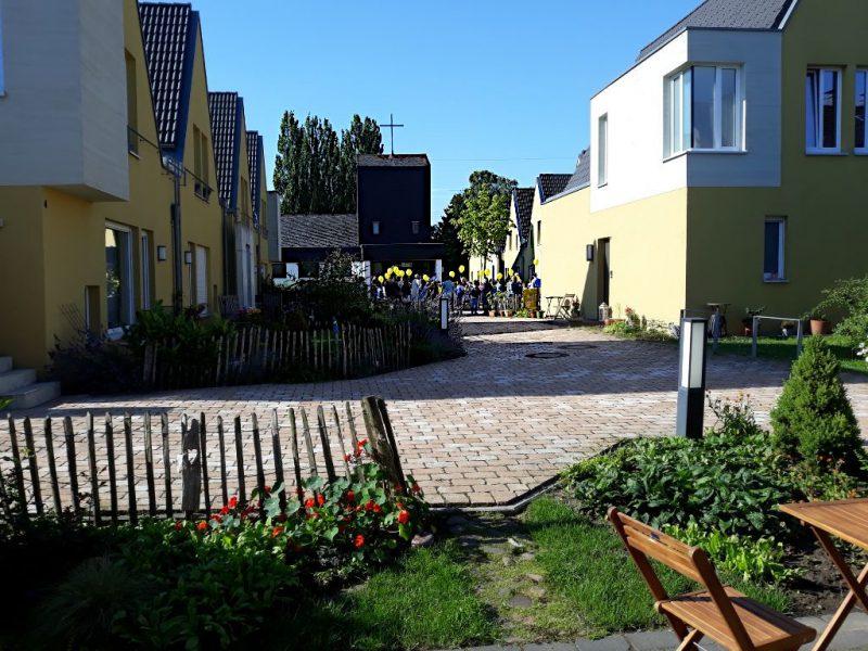 gelbe Häuser, blauer Himmel, im Hintergrund eine Kirche, davor gelbe Luftballons, die von Kindern hochgehalten werden. Im Vordergrund ein Garten mit Tisch und Stuhl, Büschen und Blüten.
