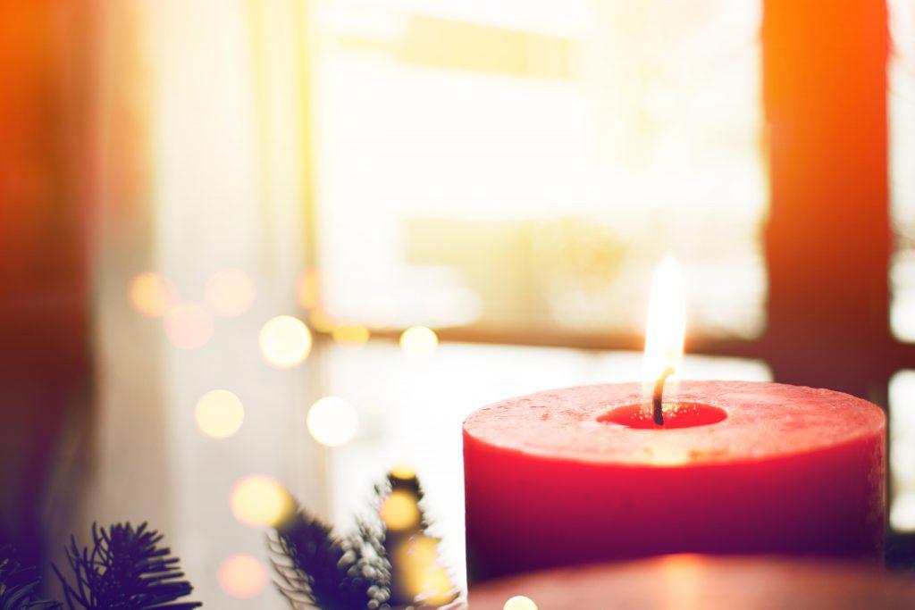 Vorne rechts eine Kerze, im Hintergrund unscharf ein Fenster mit Vorhängen rechts und links