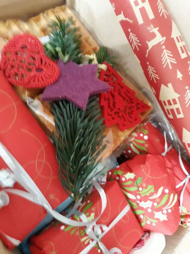 rotes Packpaier mit unterschiedlichen Mustern, kleine Päckchen mit weißen Schleifen, Stern aus Filz, drei kleine Teile: gehäkeltes Herzchen, roter Tannenbaum aus Filz; ein Tannenzweig.