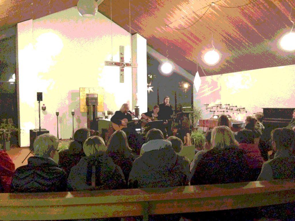 Zeltartiger Kirchenraum, Holzdecke. kugelige Lampen. Menschen sitzen war, angezogen in Bänkenund auf Stühlen und schauen nach vorne. Vorne spielen ein Mann und eine Frau Gitarre, eine andere Frau singt.