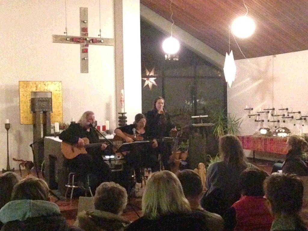 Blick auf eine Musikgruppe über dei Köpfe der Zuhörenden hinweg. Ein Mann und eine Frau spielen Gitarre, eine weitere Frau singt. Links oben: ein Kreuz hängt von der Decke. Links hinten: ein Metallgebilde steht vor der Wand (ein Tabernakel). In der Bildmitte hinten die Osterkerze. Im Glasfenster rechts spiegelt sich ein Weihnachtsstern.