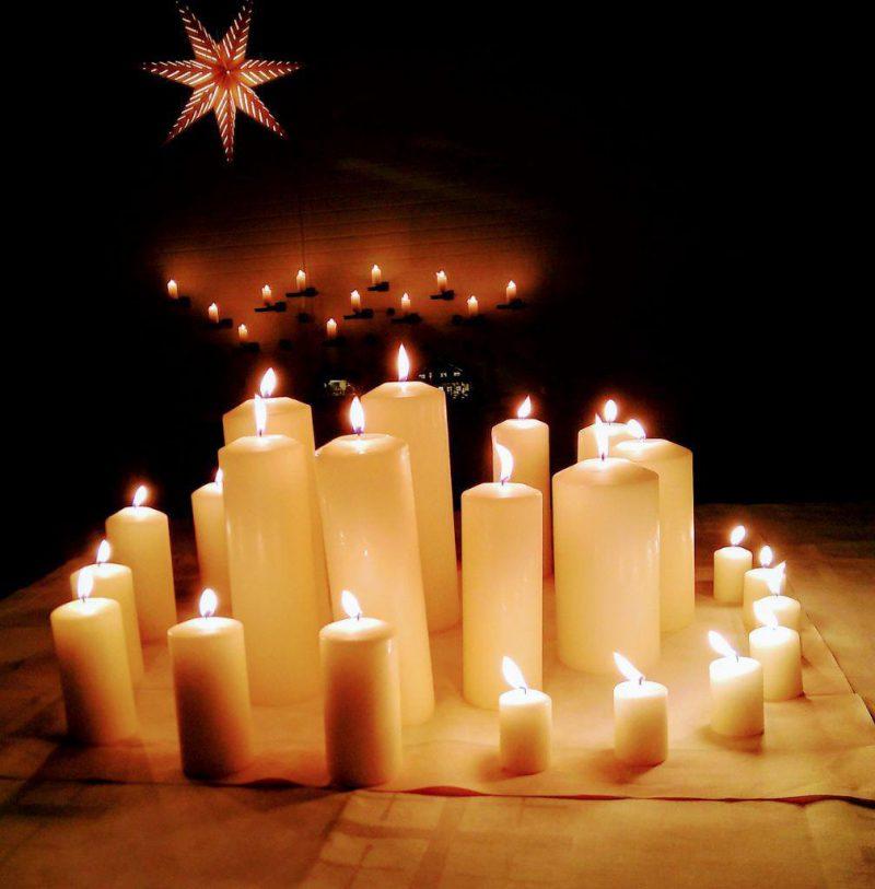 Eine Spirale aus angezündeten Kerzen im Dunkeln. Außen die kleinen, nach innen immer größer werdend. Im Hintergrund 12 Kerzen an einer Wand. Oben links ein 7-zackiger Stern.