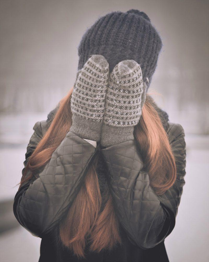 junge Frau in Winterkleidung bedeckt ihr Gesicht mit ihren Händen, die in Fäustlingen stecken.