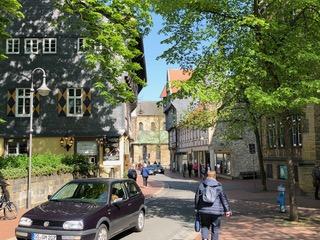 Straße mit alten Häusern, von oben ragen die begrünten Ästen eines Baumes hinein, sonnig, links vone ein Auto, Frauen gehen die Straße entlang.