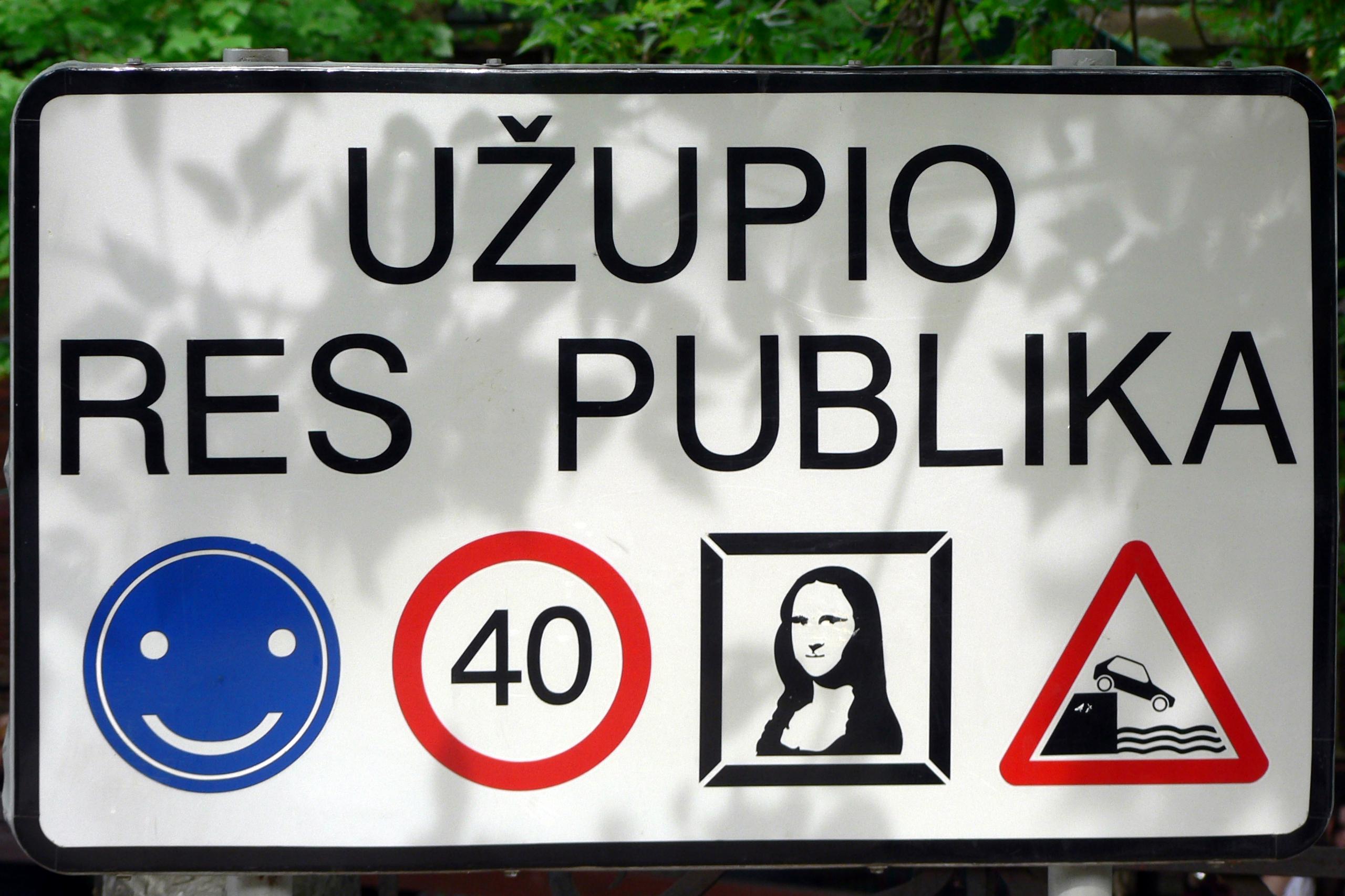Weißes Schild vor grünes Busch, Aufschrift: Uzupio Res Publika. Untere Reihe von links: Smiley, Tempo 30, Mona Lisa, Warndreieck Auto an Mauer kippt in Wasser.
