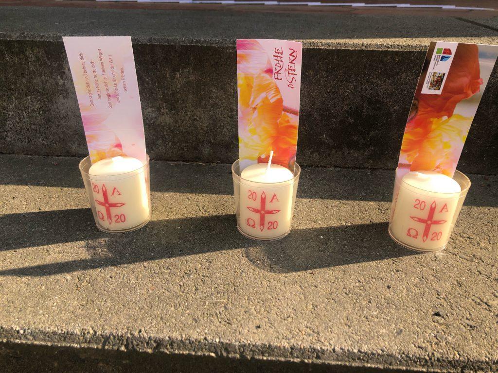 3 Plastiktöpfchen mit je einer Kerze. Auf der Kerze ein rotes Kreuz. An dem Kreuz links oben eine 20, oben rechts ein Alpha, unten links ein Omega, unten rechts eine 20. In dem Töpfchen steckt ein längliches buntes Papier mit einem Text. Treppenstufen, Sonnenschein.
