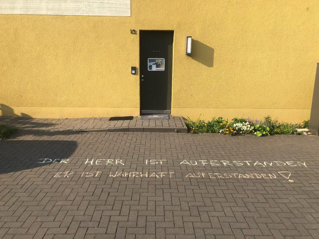 Hauswand, Metalltür, Hausnummer 13, rechts neben der Haustür ein schmaler Streifen mit Pflanzen und Blumen an der Hauswand entlang. Vor dem Haus auf der Pflasterung eines Hofes mit Kreide geschrieben: Der Herr ist auferstanden. Er ist wahrhaft auferstanden!