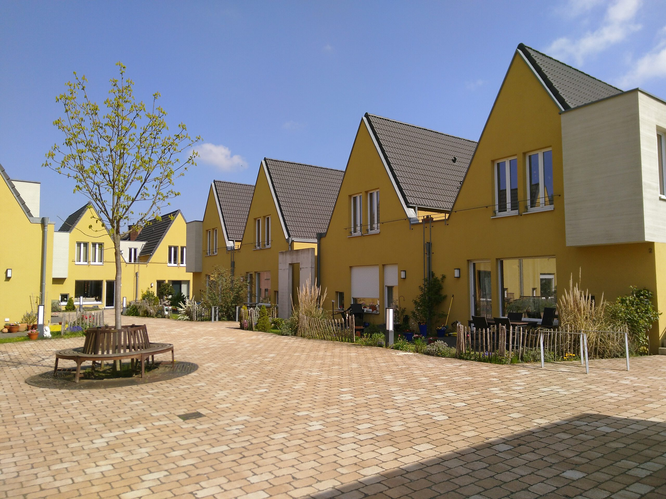 Rechts und hinten gelbe spitzgiebelige Häuser. Links mittig der noch nicht blühende Kastanienbaum mit einer Bank drumherum. Gepflasterter Hof.