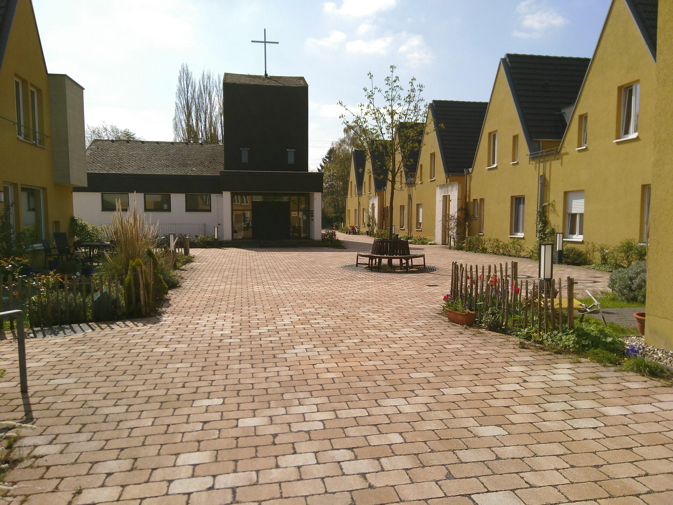 Blick auf die Kirche: Kantiger gedrungener Turm mit dünnem großen Kreuz. Links davon das Kirchengebäude mit drei Fenstern. Flankiert von gelben spitzgiebeligen Häusern. Vorgärten.