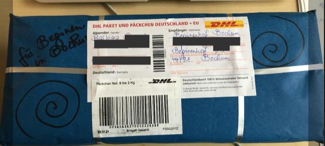 schmales rechteckiges Päckchen von oben mit DHL-Aufklebern